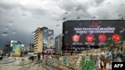FILE - A picture taken on March 17, 2020, shows a billboard displaying protective measures against the Coronavirus in the Lebanese capital Beirut.