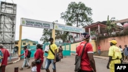 FILE - Some people wear masks as they walk by the entrance to the Yaounde General Hospital in Yaounde on March 6, 2020. Cameroon has been hit harder by the coronavirus than any other country in Central Africa.