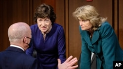 Homeland Security Secretary Alejandro Mayorkas, left, talks with Sen. Susan Collins, R-Maine, center, and Sen. Lisa Murkowski, R-Alaska, right, during a break of the Senate Appropriations committee hearing to examine domestic extremism, Wednesday,…