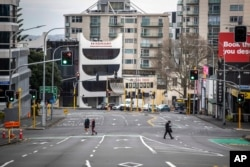FILE - People cross nearly empty streets in the central business district of Auckland, New Zealand, Aug. 27, 2021.
