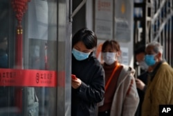 People wait in a queue to get temperature check before entering a bank in Beijing, March 11, 2020.