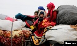 FILE - Internally displaced Syrians from western Aleppo countryside, ride on a vehicle with belongings in Hazano near Idlib, Syria, Feb. 11, 2020.