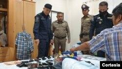 Uno de los sujetos arrestados por tráfico humano aparece sentado sobre su cama con varias armas de fuego, una muestra de lo peligroso de la industria pesquera en Tailandia.