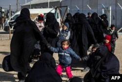 Women and children are seen in the Kurdish-run al-Hol camp which holds suspected relatives of Islamic State (IS) group fighters, in Hasakeh governorate in northeastern Syria, Jan. 28, 2021.
