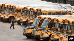 A worker passes public school buses parked at a depot in Manchester, New Hampshire, April 27, 2020. Children continue to be taught with remote learning while buildings are closed.