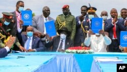 FILE - Sudan's transitional authorities and a rebel alliance sign a peace deal initialed in August that aims to put an end to the country's decades-long civil wars, in a televised ceremony in Juba, South Sudan, Oct. 3, 2020.