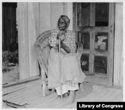FILE - Lucinda Davis, guessed to be 89 years-old at the time, sits on the front porch of her home in Tulsa, Oklahoma, Aug. 16, 1937. She was the former slave of a full-blooded Muscogee Creek farmer named Tuskaya-hiniha. (Library of Congress)