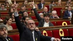 FILE - Lluis Corominas of Junts per Catalunya and Sergi Sabria of Republican Left of Catalonia (ERC) vote during a debate in the regional parliament in Barcelona, Spain, May 4, 2018.