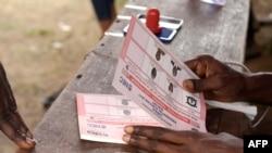利比里亚全国选举委员会的一名成员在蒙罗维亚为总统决选准备选票。(2017年12月26日)
