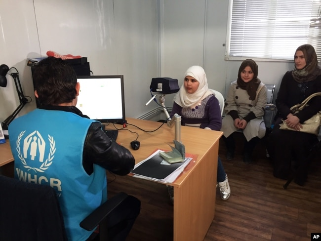 FILE - Biometric identification systems are being used in novel ways. In this photo, a Syrian refugee girl poses for a biometric iris scan in a U.N. office in Amman, Jordan, an intial step in her efforts to be approved for resettlement in the West. Somaliland has become the first to employ iris-scanning technology to identify voters.