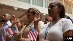 People take the oath as the US Citizenship and Immigration Services welcomes 200 new citizens from nearly 50 countries during a ceremony in honor of Independence Day at the New York Public Library, July 3, 2018, in New York.