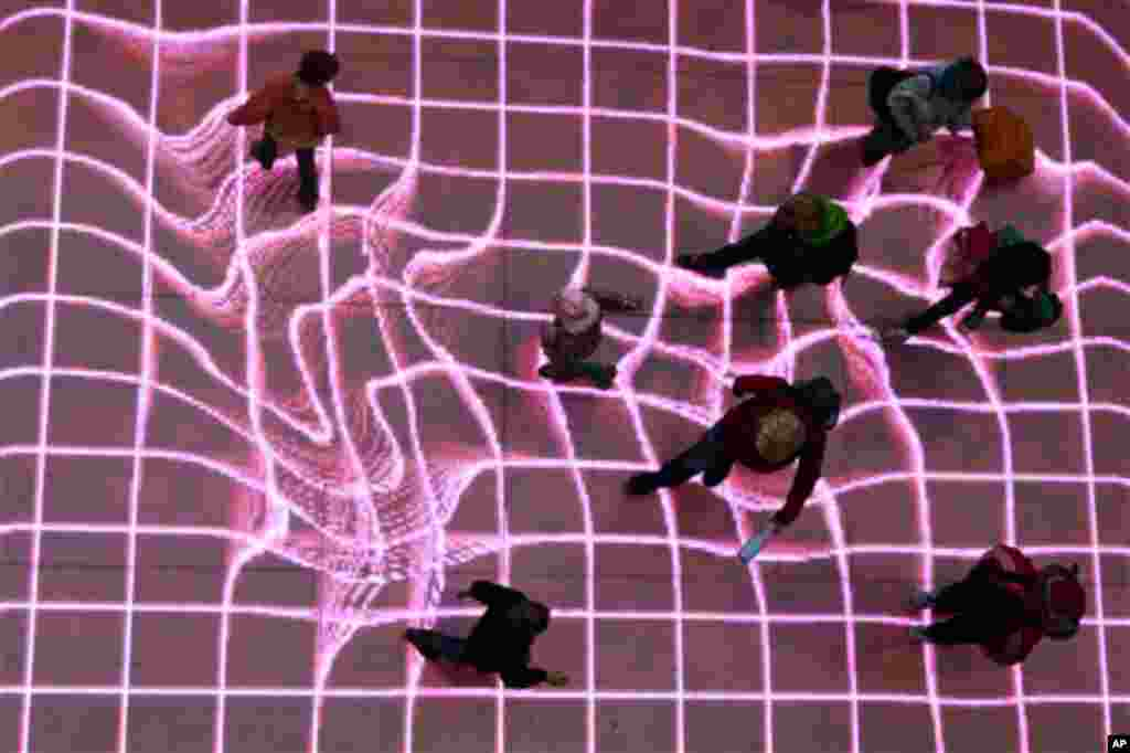 "People walk over the interactive installation ""Onskebronn"", Norwegian for wishing well, at A central station in Berlin, Germany, Thursday, Oct. 14, 2010. The moving paths of visitors are followed on that LED-platform and retraced as reprocessed projection"