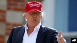 """Donald Trump habla conlos periodistas luego de llegar en helicóptero al Abierto Británico de Golf, en Escocia. El letrero en su gorra lee: """"Hagamos a Estados Unidos grande de nuevo""""."""