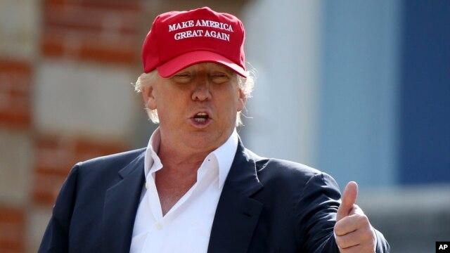 Donald Trump habla conlos periodistas luego de llegar en helicóptero al Abierto Británico de Golf, en Escocia. El letrero en su gorra lee: