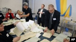 Election commission officials count ballots at a polling station in Kiev, Ukraine, Sunday, Oct. 28, 2012. Ukrainians are electing a parliament on Sunday in a crucial vote tainted by the jailing of top opposition leader Yulia Tymoshenko and fears of electi