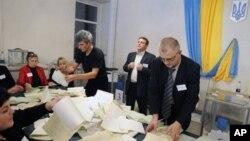 Komisi Pemilu Ukraina menghitung surat suara yang masuk di sebuah TPS di Kiev, Ukraina (28/10).