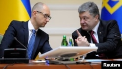 Presiden Ukraina Petro Poroshenko berbincang dengan PM Arseny Yatseniuk di sela rapat kabinet di Kyiv, Ukraina Rabu (10/9).