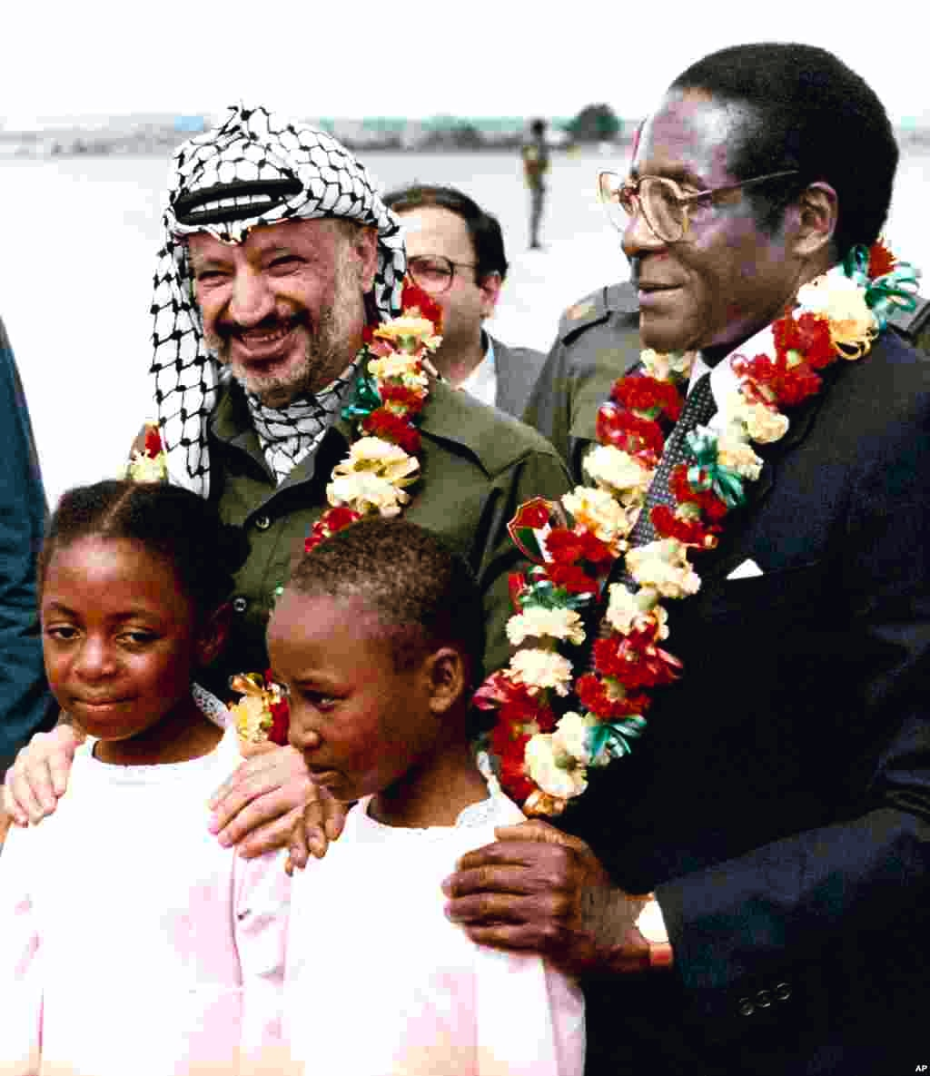 Zimbabwean Prime Minister Robert Mugabe, right, and Yasser Arafat, left, pose for photos after being garlanded by two 10-year-old school girls, Jean Chitanda, left, and Tsitsi Chikasha, on Arafat's arrival at Harare Airport, Zimbabwe, April 14, 1987, to attend a meeting of the Non-aligned Movement's Committee on Palestine.