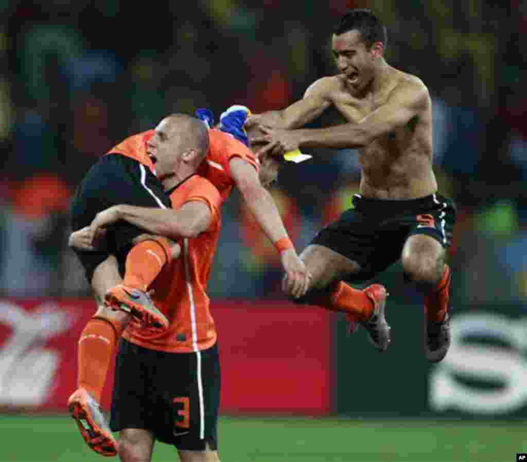 Netherlands' John Heitinga, bottom, carries teammate Wesley Sneijder, top, as teammate Giovanni van Bronckhorst celebrates near them at the end of the World Cup quarterfinal soccer match between the Netherlands and Brazil at Nelson Mandela Bay Stadium in