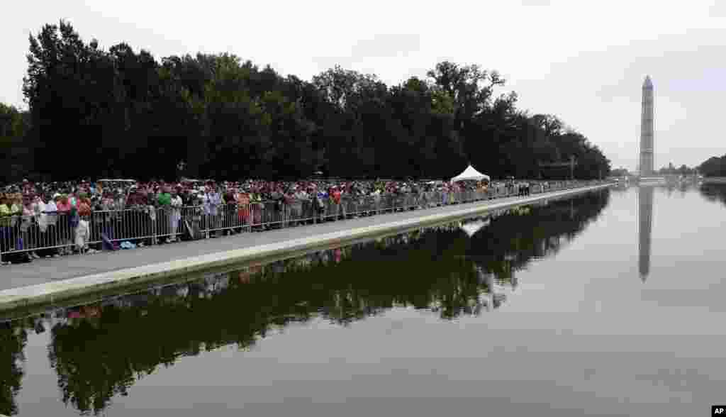 People gather around the reflecting pool near the Lincoln Memorial, Aug. 28, 2013, to listen to President Barack Obama speak during the 50th anniversary of the March on Washington.