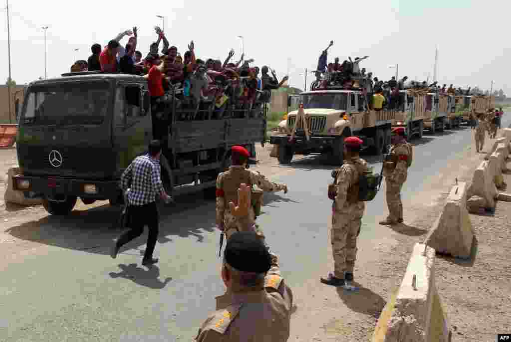 Iraqi men who volunteered to join the fight against a major offensive by jihadists in northern Iraq stand on army trucks as they leave a recruiting center in the capital Baghdad. Iraqi forces clashed with militants advancing on the city of Baquba, just 60 kilometers (40 miles) north of Baghdad.