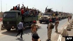 Kaum lelaki Irak yang secara sukarela bergabung melawan serangan kelompok jihadis di Irak utara naik truk tentara ketika mereka meninggalkan pusat perekrutan mereka di ibukota Baghdad, 13/6/2014.