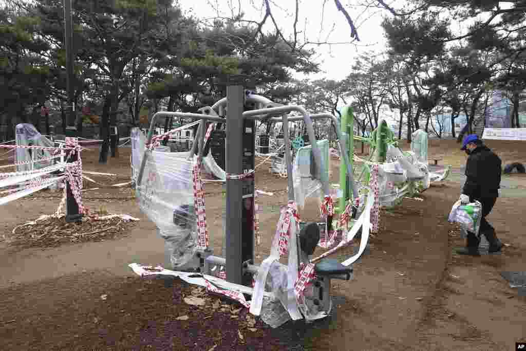 Exercise equipment is covered up, as the use of public sports facilities is banned amid social distancing rules at a park in Goyang, South Korea.