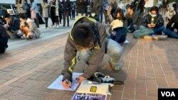 集會人士用手機翻譯程式,以印尼文寫留言聲援被逐印傭作家Yuli。(美國之音 湯惠芸拍攝)