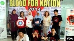 "Sylvie Young (berdiri, nomor 2 dari kanan mengenakan blouse putih) bergambar bersama para relawan ""Blood For Nation"" di Universitas Muhammadiyah Yogyakarta, Rabu, 7 Mei 2014 (Foto: VOA/Munarsih Sahana)"
