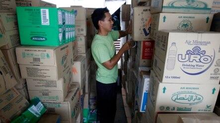 志愿人员堆起成箱矿泉水,准备送往马来西亚暴雨灾区(2014年12月27日)