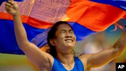 Cambodia's Chov Sotheara celebrates her victory over Thailand's Suree Porn Pimpak to win the gold medal in the women's under 44-kilogram wrestling match at South East Asian Games in Yangon, Myanmar, Friday, Dec 13, 2013. (AP Photo/Gemunu Amarasinghe)