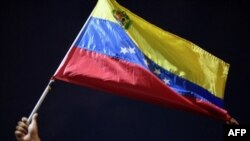 Un hombre muestra una bandera nacional mientras familiares y amigos de migrantes venezolanos que murieron cuando se hundió un barco que los transportaba a Trinidad y Tobago, protestan en Güiria, Venezuela, el 18 de diciembre de 2020.
