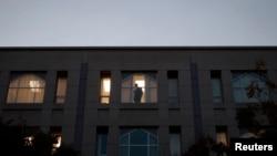 FILE - A worker looks out a window inside Pakistan's embassy in Washington, Nov. 5, 2007.