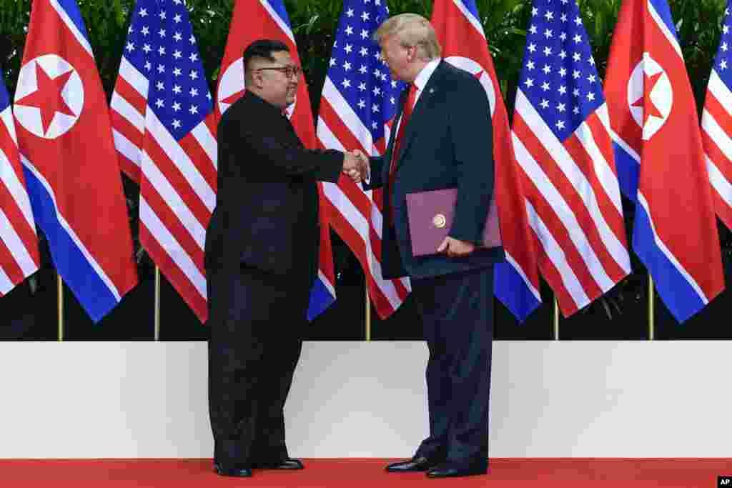 Shugaban Amurka Donald Trump da shugaban Koriya Ta Arewa Kim Jong Un suna shan hannu bayan sa hannu a yarjejeniya a taron kolin da suka gudanar a otel din Capella Hotel dake tsibirin Sentosa, Singapore, Juni 12, 2018.