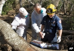 Paige Beard, from left, Curtis Skene and Montecito Fire Paramedic Kurt Hickman try to identify a photo album found in the debris near East Valley Road in Montecito, Calif., Jan. 25, 2018. Skene fought back tears as firefighters uncovered old photographs of his father in his home.