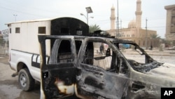 A burned police vehicle left in the main street of Fallujah after clashes between Iraqi security forces and al-Qaeda fighters in Fallujah, 40 miles (65 kilometers) west of Baghdad, Jan. 5, 2014