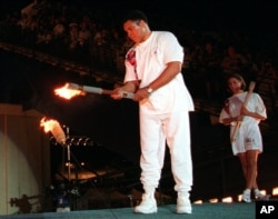 FILE - In this July 19, 1996, file photo, American swimmer Janet Evans looks on as Muhammad Ali lights the Olympic flame during the 1996 Summer Olympic Games opening ceremony in Atlanta.