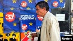 Чоловік у Скоп'є проходить повз плакати, які агітують за угоду з Грецією, що могла б відкрити шлях для вступу Македонії у Європейський Союз. Фото 28 вересня 2018 р.