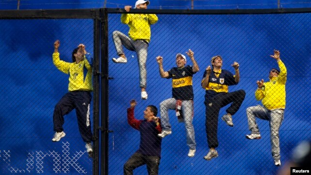 Boca Juniors' fans climb a fence during an Argentine First Division soccer match in Buenos Aires, May 5, 2013.