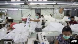 科學家建議在室內要戴口罩以避免病毒傳播。圖為戴口罩的緬甸工人在仰光的一家工廠內縫製手術用口罩。 2020年5月8日圖片。