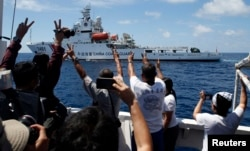 FILE - A Chinese Coast Guard vessel maneuvers to block a Philippine government supply ship with members of the media aboard at the disputed Second Thomas Shoal, part of the Spratly Islands, in the South China Sea.
