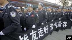 Members of China's peacekeeping police contingent, who have been to Haiti, hold a banner as they wait in line to attend a funeral for eight Chinese peacekeepers killed in the Haiti earthquake, at Babaoshan Revolutionary Cemetery in Beijing, January 20, 20