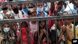 Anak-anak menunggu pembagian makanan gratis di sebuah pemukiman kumuh saat karantina wilayah untuk mencegah penularan virus corona, di Mumbai, India, 18 April 2020.