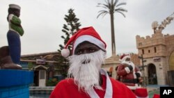 Mamadou Ngueye, who dresses as Santa Claus, waits for a guest to take a picture with at the amusement park Darkar, Senegal, Dec. 19 2015. Ngueye, is one of many Peres Noels, or Father Christmases, seen in Senegal's capital.