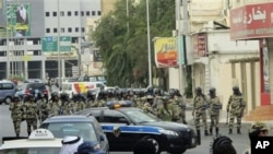 Saudi riot police gather as Saudi Shi'ite protesters, unseen, chant slogans during a demonstration in Qatif, March 11, 2011