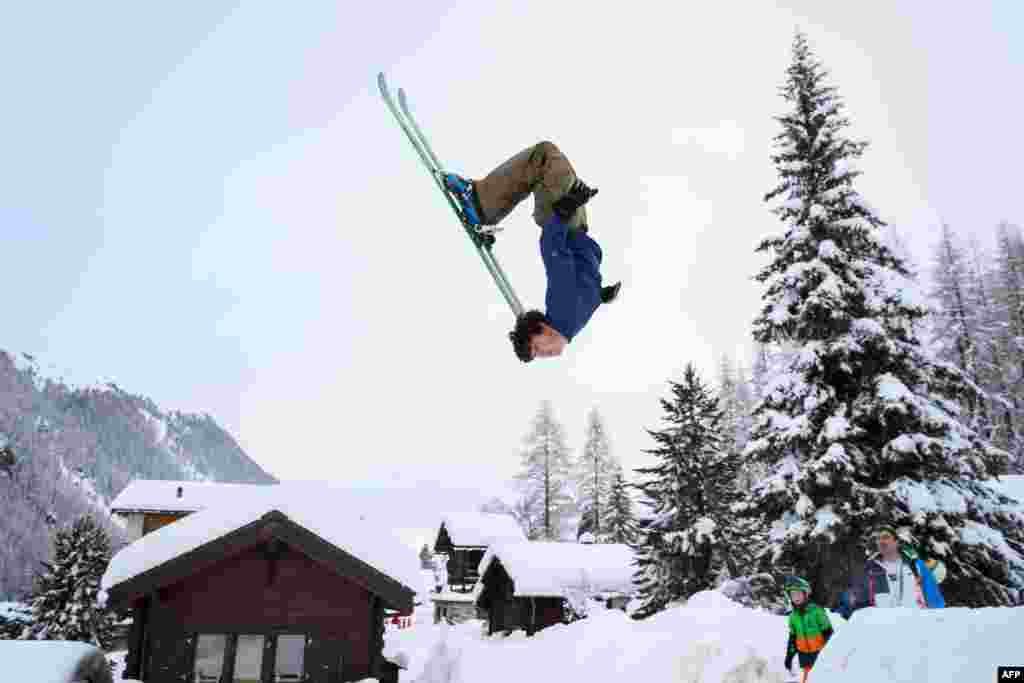 Teenager Luc makes a backflip on skis in the small resort of Zinal, Swiss Alps, after the access road which was cut by heavy snowfall reopened.