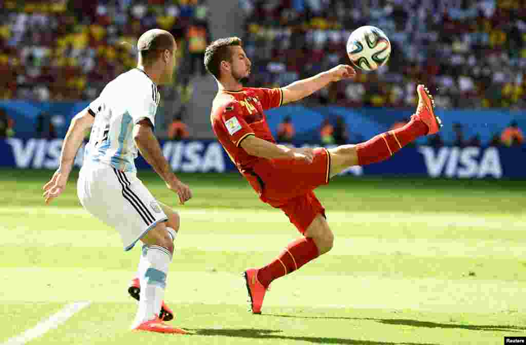 Belgium's Dries Mertens kicks the ball as Argentina's Rodrigo Palacio looks on at the Brasilia national stadium in Brasilia, July 5, 2014.