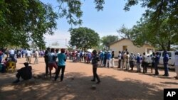 Wapiga kura wasubiri kupiga kura zao katika kituo cha kura cha Gaberone, Botswana, wakati wa uchaguzi mkuu Ijuma Okt 24.