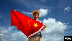 一位中国警察在在南中国海的西沙群岛上展示国旗(2014年9月14日)