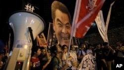 2014年9月25日香港学生举着丑化了的香港特首梁振英图像上街罢课
